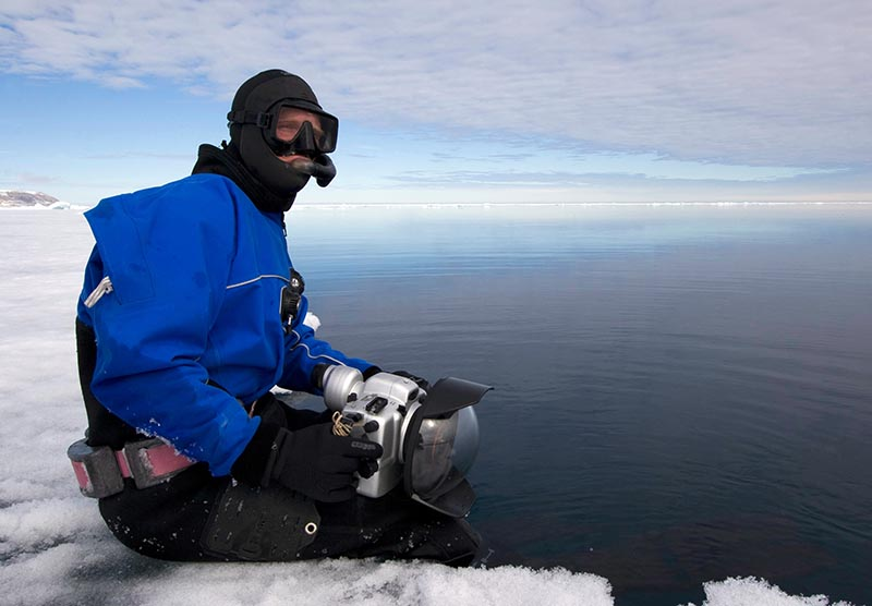 Photographer Paul Nicklen sitting on the edge of an ice floe.